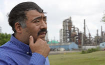 Juan Flores pauses while poses for a photograph while standing in a small park near a refinery along the Houston Ship Channel Monday, March 23, 2020, in Houston. Flores is working on a project to install air monitors at schools, not to warn children when the air was too bad to play outside, but alert them when plant emissions were low enough to make that safe. (AP Photo/David J. Phillip)