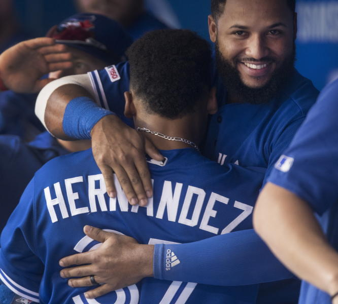 Toronto Blue Jays' Teoscar Hernandez gets a hug from teammate Richard Urena after he hit a home run against the Tampa Bay Rays in a baseball game in Toronto Saturday Sept. 28, 2019. (Fred Thornhill/The Canadian Press via AP)