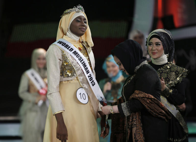In this Wednesday, Sept. 18, 2013 photo, Indonesian parliament member Wardatul Asriah, center, puts a sash on Obabiyi Aishah Ajibola, left, of Nigeria after being named World Muslimah 2013 as World Muslimah 2012 Nina Septiani of Indonesia looks on during the 3rd Annual Award of World Muslimah, a competition billed as the Islamic alternative to Miss World pageant, in Jakarta, Indonesia. Beauty queens and backstage drama may seem inevitable, but at this year's Miss World competition, something more serious than hair-pulling and name-calling has come from host country Indonesia: Muslim hardliners have threatened to hijack the competition despite major concessions from the government and organizers. (AP Photo/Dita Alangkara)