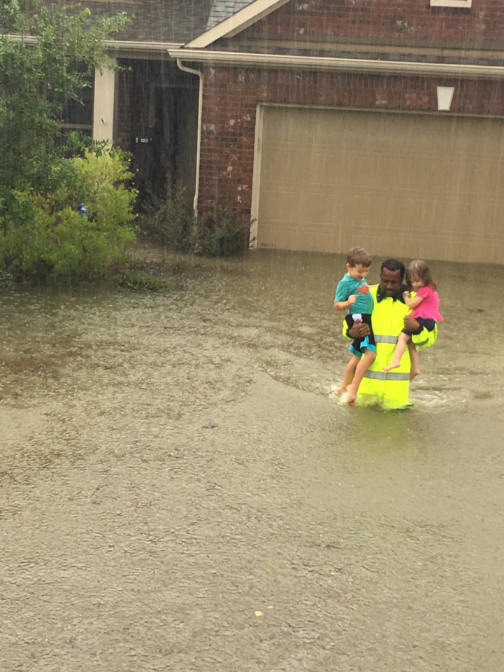 <p>Sheriff's Deputy R. Johnson rescuing two children from flooding. Credit: HSCOTexas </p>