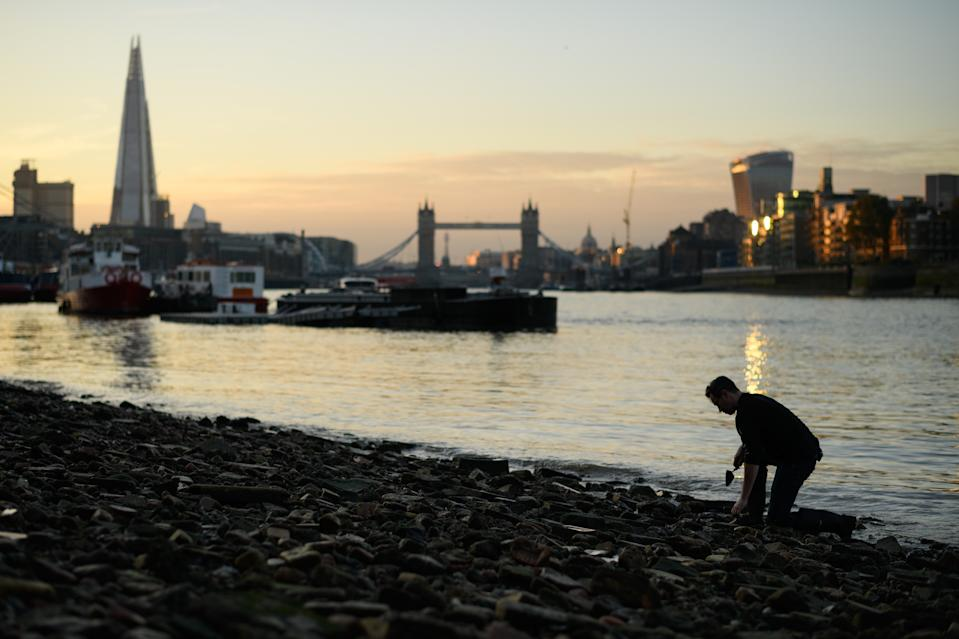 LONDON, ENGLAND - OCTOBER 20: Tower Bridge is seen in the distance as Mudlark Jason Sandy searches the shoreline of the River Thames for historical items on October 20, 2018 in London, England. Moving to London eleven years ago, US-born Jason Sandy fell in love with the history that was available to explore on his doorstep and now has over 35,000 followers on his instagram feed