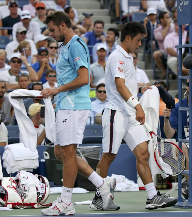 Stan Wawrinka, of Switzerland, left, and Kei Nishikori, of Japan, cross paths as they walk to their benches during a break between games during the quarterfinals of the 2014 U.S. Open tennis tournament, Wednesday, Sept. 3, 2014, in New York. (AP Photo/Mike Groll)