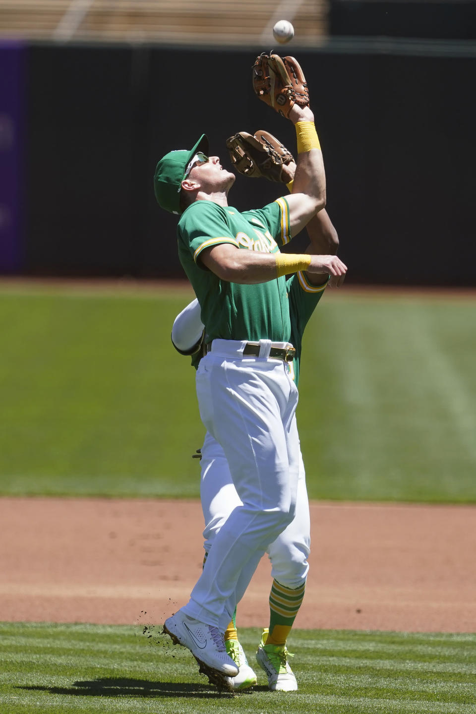 Oakland Athletics third baseman Matt Chapman, foreground, catches a pop out hit by Kansas City Royals' Carlos Santana in front of second baseman Tony Kemp during the first inning of a baseball game in Oakland, Calif., Sunday, June 13, 2021. (AP Photo/Jeff Chiu)