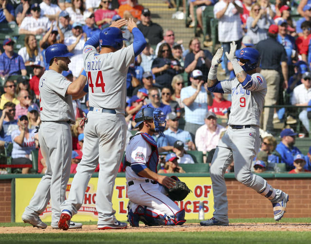 Chicago Cubs' Mark Zagunis (2) and Anthony Rizzo (44) greet Javier Baez (9) at home plate after Baez' home run against the Texas Rangers in the fifth inning of a baseball game Thursday, March 28, 2019, in Arlington, Texas. (AP Photo/ Richard W. Rodriguez)