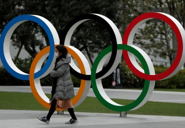 FILE PHOTO: A woman wearing a protective face mask, following an outbreak of the coronavirus disease, walks past the Olympic rings in front of the Japan Olympics Museum, in Tokyo