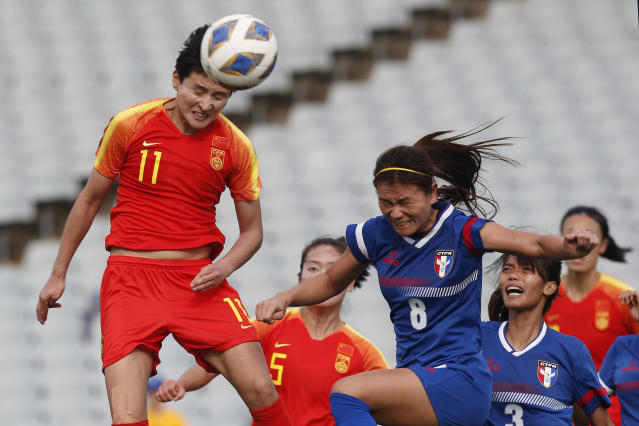 Wang Shanshan of China, left, goes up for a header against Taiwan's Wang Hsiang-Huei during their Olympic soccer qualifying match in Sydney, Friday, Feb. 10, 2020. (AP Photo/Steve Christo)