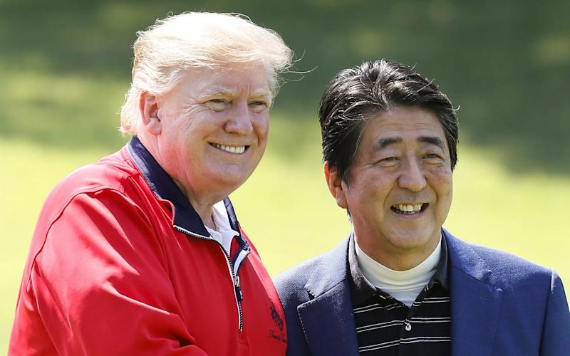 US President Donald Trump and Shinzo Abe, Japan's prime minister, pose for photographs at Mobara Country Club in Chiba Prefecture - EPA