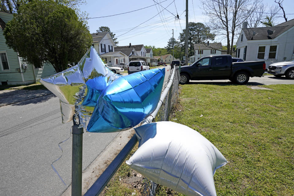 Balloons are seen tied to a fence in Elizabeth City, N.C., Thursday, April 22, 2021 at the scene where a North Carolina deputy shot and killed a Black man while executing a search warrant on Wednesday, authorities said. (AP Photo/Gerry Broome)
