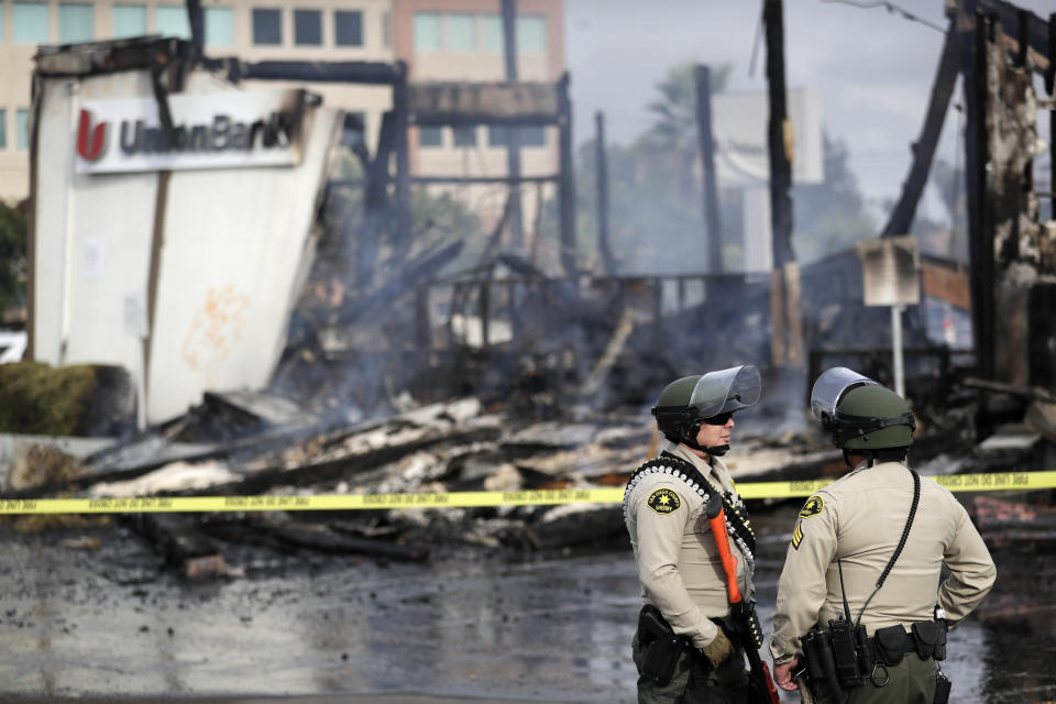 San Diego County sheriff officers stand guard in front of a burning bank building after a protest over the death of George Floyd, Sunday, May 31, 2020, in La Mesa, Calif. Protests were held in U.S. cities over the death of Floyd, a black man who died after being restrained by Minneapolis police officers on May 25. (AP Photo/Gregory Bull)