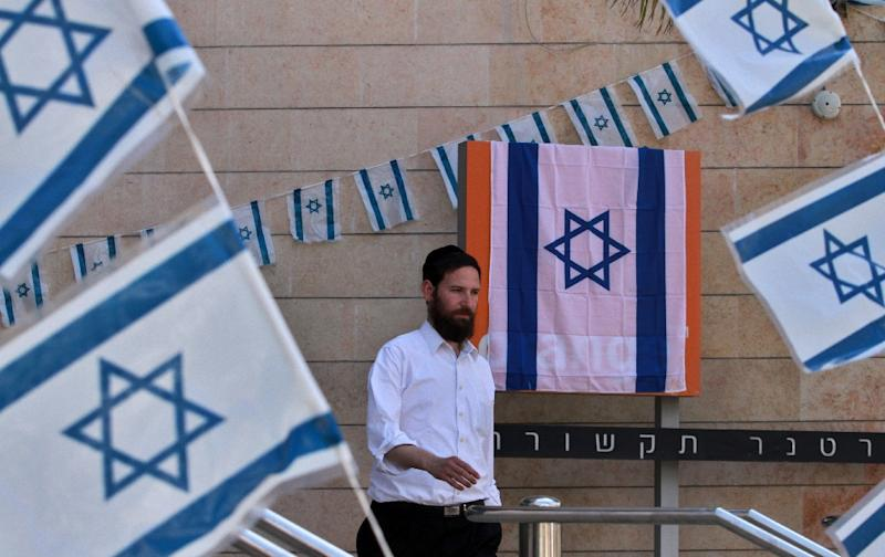 Israeli flags are seen outside the office of telecom operator Partner Communications -- which operates under the Orange brand -- in Rosh Haain, on June 11, 2015 (AFP Photo/Gil Cohen Magen)