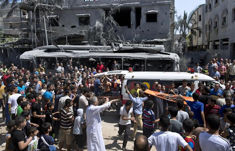 Palestinians crowd around an ambulance in Gaza City as a deceased victim of an Israeli strike is removed from the rubble of a house on August 20, 2014 (AFP Photo/Roberto Schmidt)