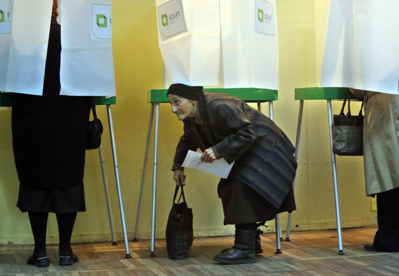 Georgian woman crouches as she leaves a voting booth during the presidential election in Tbilisi, Georgia, Sunday, Oct. 27, 2013. Georgians are voting Sunday for a president to succeed Mikhail Saakashvili, who during nearly a decade in power has turned this former Soviet republic into a fledgling democracy and and a staunch U.S. ally. (AP Photo/Sergei Grits)