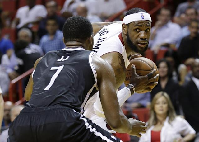 Miami Heat forward LeBron James, right, looks for an open teammate past Brooklyn Nets guard Joe Johnson (7) during the first half of an NBA basketball game, Wednesday, March 12, 2014, in Miami. (AP Photo/Wilfredo Lee)