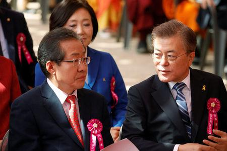 Moon Jae-in, presidential candidate of the Democratic Party of Korea, talks with Hong Joon-pyo, presidential candidate of the Liberty Korea Party, during a ceremony celebrating birthday of Buddha at Jogye temple in Seoul