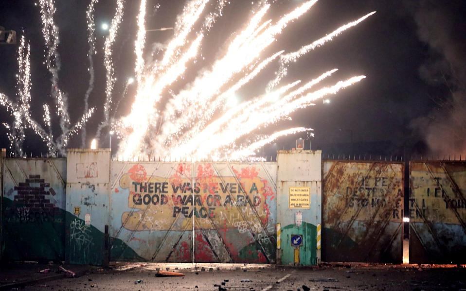 Fireworks explode at the peace wall on Lanark Way in west Belfast - AP