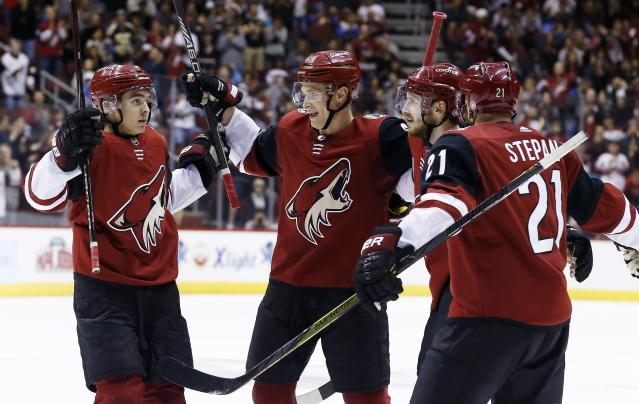 Arizona Coyotes defenseman Oliver Ekman-Larsson, second from right, celebrates his goal against the Vancouver Canucks with center Clayton Keller, left, defenseman Jakob Chychrun, second from left, and center Derek Stepan (21) during the second period of an NHL hockey team Sunday, March 11, 2018, in Glendale, Ariz. (AP Photo/Ross D. Franklin)
