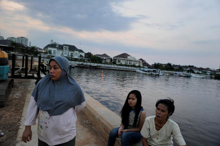 Residents gather along a dyke in Jakarta as construction of the Indonesian capital's sea wall begins, October 9, 2014