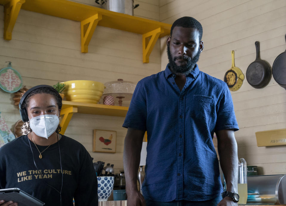 "This image released by Warner Bros. Entertainment shows director Cierra Glaude, left, with Kofi Siriboe on the set of ""Queen Sugar."" When the series debuted in 2016, Glaude worked as a production assistant on the show. Five years later, she's been promoted to director for season five on the Oprah Winfrey Network series. (Skip Bolen/2020 Warner Bros. Entertainment via AP)"