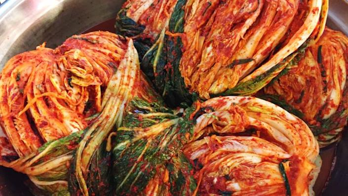 whole heads of cabbage kimchi in bowl