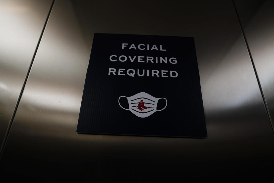 A sign showing that facial coverings are required is seen in a Boston Red Sox' elevator during a spring training baseball game against the Atlanta Braves on Monday, March 1, 2021, in Fort Myers, Fla. (AP Photo/Brynn Anderson)