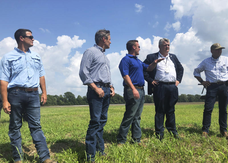 Gov. Bill Lee, second left, stands in Lauderdal County, Tenn., as he was participating an aerial tour over flooded crop land Wednesday, July 17, 2019. Lee took the aerial tour of flooded crop land in western Tennessee and promised support to farmers struggling with when to plant. (AP Photo/Kimberlee Kruesi)