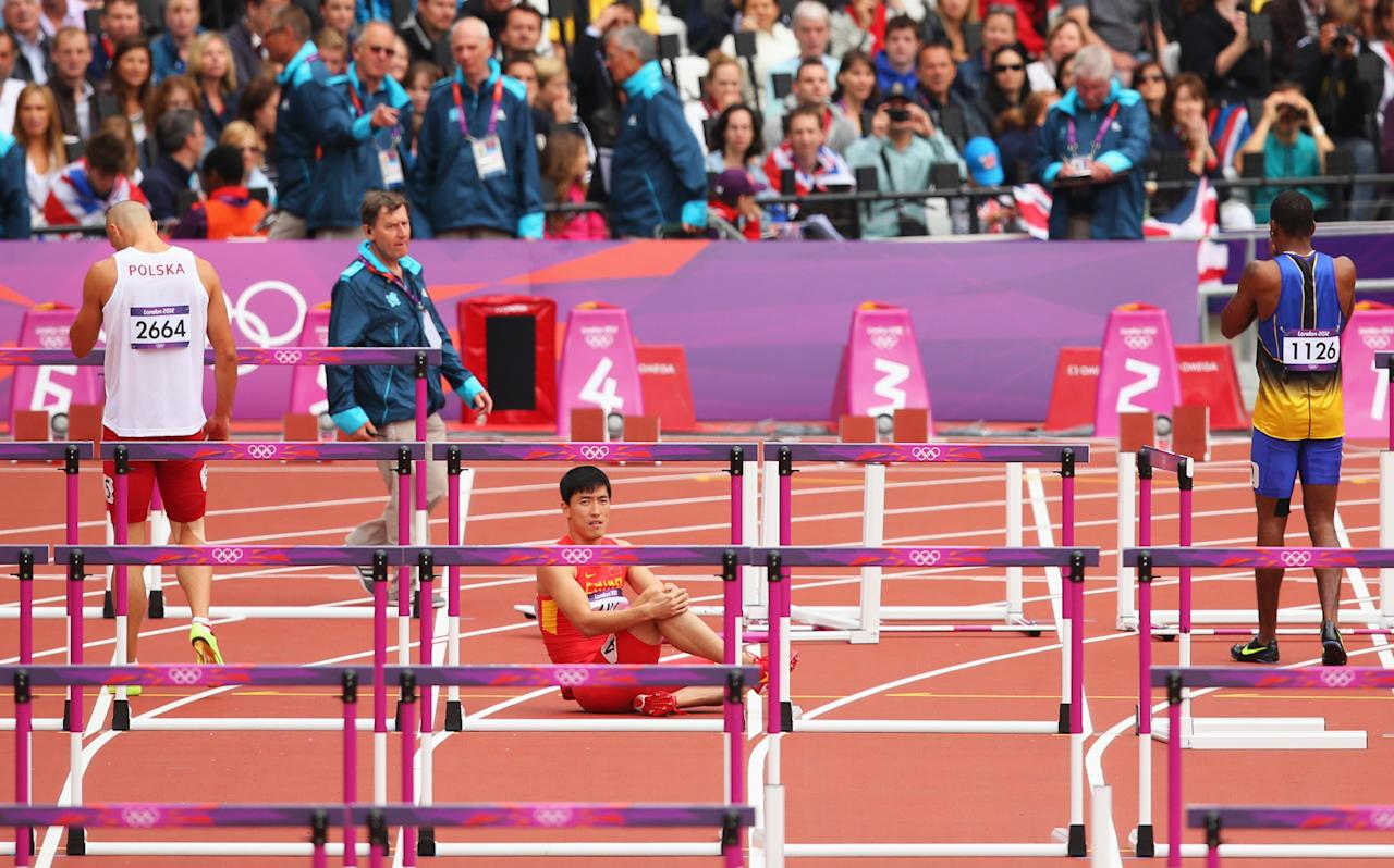 Xiang Liu of China sits on the track after getting injured in the Men's 110m Hurdles Round 1 Heats on Day 11 of the London 2012 Olympic Games at Olympic Stadium on August 7, 2012 in London, England.  (Photo by Cameron Spencer/Getty Images)