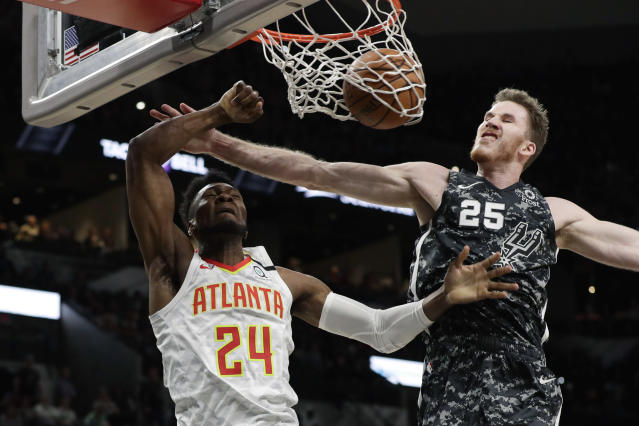 Atlanta Hawks forward Bruno Fernando (24) scores past San Antonio Spurs center Jakob Poeltl (25) during the first half of an NBA basketball game in San Antonio, Friday, Jan. 17, 2020. (AP Photo/Eric Gay)