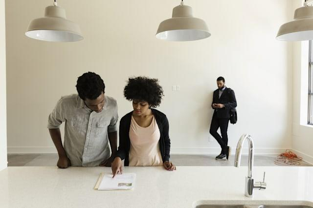 Couple reading paperwork in new house