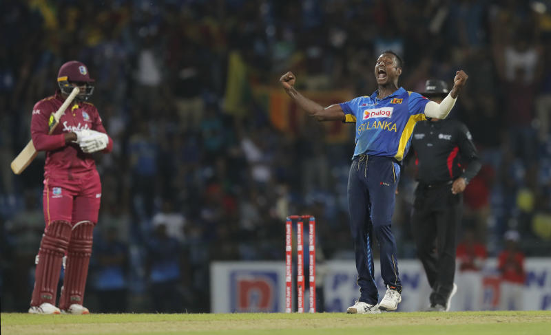 Sri Lanka's Angelo Mathews, right, celebrates the his team's victory over West Indies' by six runs as Sheldon Cottrell looks on during the third one day international cricket match between Sri Lanka and West Indies in Pallekele, Sri Lanka, Sunday, March 1, 2020. (AP Photo/Eranga Jayawardena)