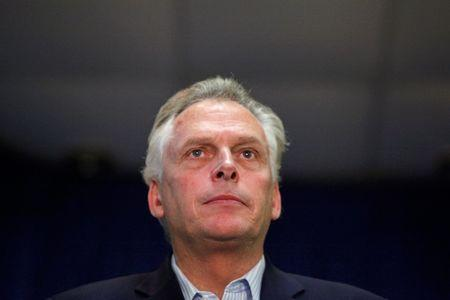 McAuliffe stands onstage during campaign rally in Dale City, Virginia
