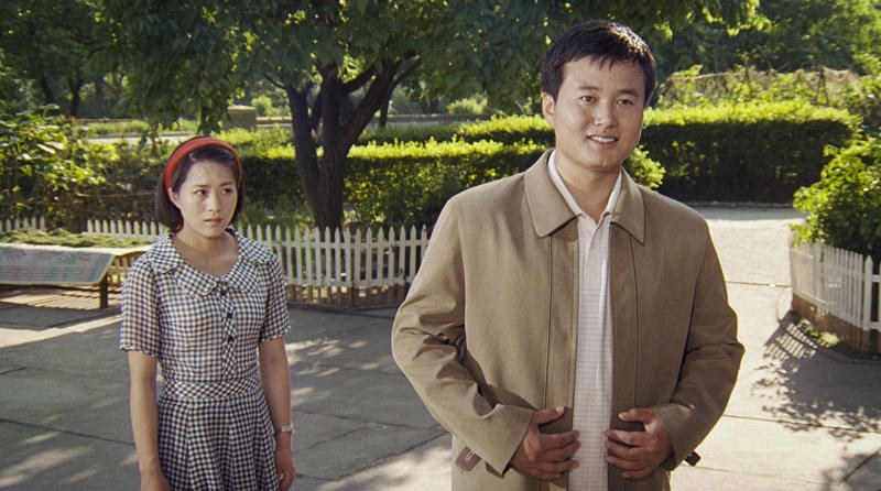 """In this image made out of film """"Comrade Kim Goes Flying"""" released by Another Dimension of An Idea/Koryo Group, Comrade Kim Yong Mi, left, played by Han Jong Sim and Pak Jang Phil played by Pak Chung Guk are together at a park. It's a classic tale of a small town girl who follows her dreams to the big city. But in this case, the girl is a North Korean coal miner, the big city is Pyongyang and her dream is to become a high-flying trapeze artist. """"Comrade Kim Goes Flying,"""" a collaboration between a North Korean director and two European filmmakers, makes its world premiere Saturday, Sept. 8, 2012 at the Toronto International Film Festival before it heads to Pyongyang later this month for its North Korean debut. (AP Photo/Courtesy of Another Dimension of An Idea/Koryo Group) EDITORIAL USE ONLY"""