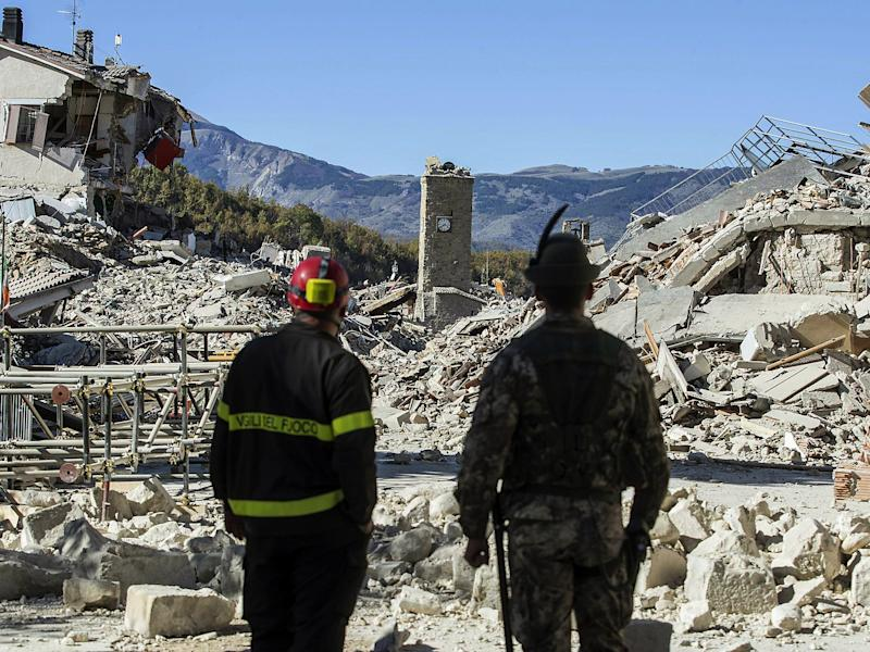 A firefighter and an alpine soldier look at rubble in the hilltop town of Amatrice as an earthquake with a preliminary magnitude of 6.6 struck central Italy: Massimo Percossi/ANSA via AP
