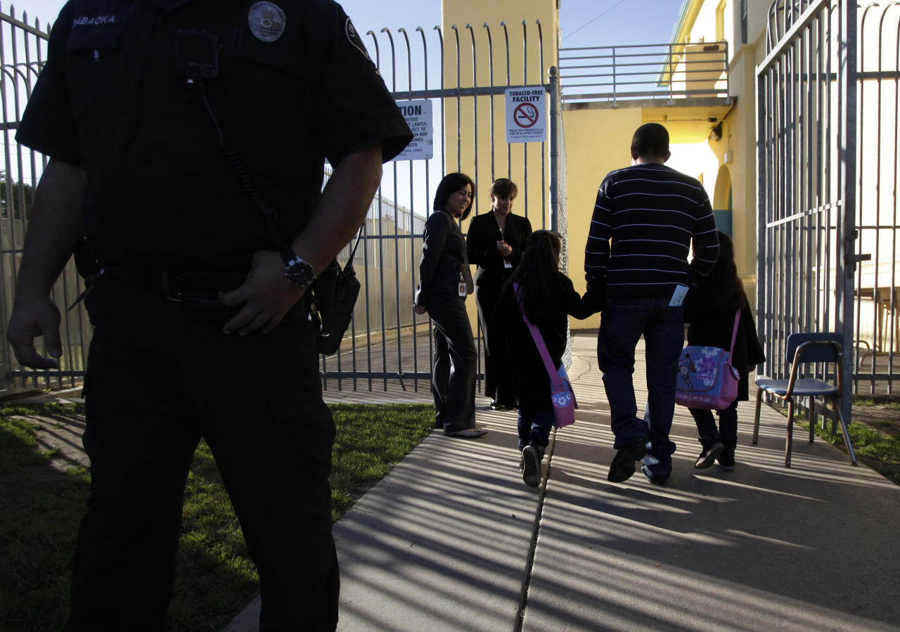 An adult accompanies two students into Miramonte Elementary School in Los Angeles on Thursday, Feb. 9, 2012. Children are returning to a Los Angeles-area elementary school where the entire staff has been replaced following the arrests of two former teachers on charges of committing lewd acts with students in class. (AP Photo/Jae C. Hong)