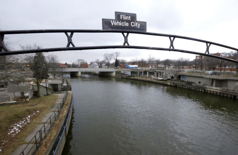 FILE - This Jan. 26, 2016 file photo shows a sign over the Flint River noting Flint, Mich., as Vehicle City. The U.S. Environmental Protection Agency says states are taking action to address the risk of lead in drinking water but more needs to be done to share key information with the public. (AP Photo/Carlos Osorio, File)