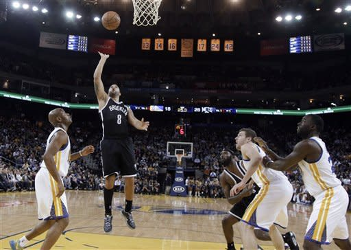 Brooklyn Nets' Deron Williams (8) scores against the Golden State Warriors during the first half of an NBA basketball game in Oakland, Calif., Wednesday, Nov. 21, 2012. (AP Photo/Marcio Jose Sanchez)