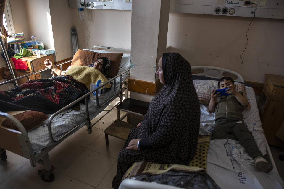 Ihsan Al-Masri, 24, left, rests at the Shifa hospital in Gaza City, May 13, 2021, as her son plays on a mobile phone on the bed next to her. Ihsan is receiving treatment for wounds caused by a May 10 Israeli strike that hit a nearby her family house in town of Beit Hanoun. Just weeks ago, the Gaza Strip's feeble health care system was struggling with a runaway surge of coronavirus cases. Now doctors across the crowded coastal enclave are trying to keep up with a very different crisis: blast and shrapnel wounds, cuts and amputations. (AP Photo/Khalil Hamra)