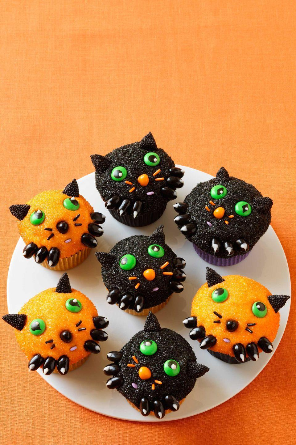 """<p>These cute kitten cupcakes are perfect for a fun Halloween bash full of younger kids.</p><p><a href=""""https://www.womansday.com/food-recipes/food-drinks/recipes/a11375/kitten-cupcakes-recipe-wdy1012/"""" rel=""""nofollow noopener"""" target=""""_blank"""" data-ylk=""""slk:Get the Kitten Cupcakes recipe."""" class=""""link rapid-noclick-resp""""><em>Get the Kitten Cupcakes recipe.</em></a></p>"""