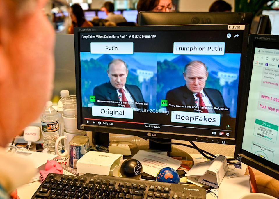 """A journalist views video manipulated with artificial intelligence to potentially deceive viewers, or """"deepfake"""" (AFP via Getty Images)"""