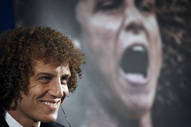 PSG newly recruited Brazilian defender David Luiz poses in front of a giant poster of his portrait during his official presentation, on August 7, 2014 in Paris (AFP Photo/Lionel Bonaventure )