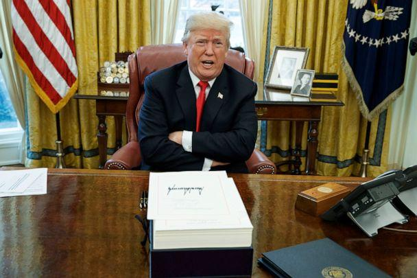 PHOTO: President Donald Trump speaks with reporters after signing a tax bill and resolution in the Oval Office of the White House in Washington. (Evan Vucci/AP, FILE)