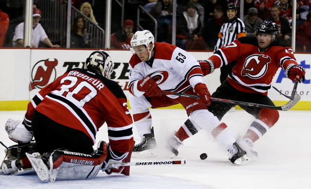 Carolina Hurricanes left wing Jeff Skinner, center, skates against New Jersey Devils goalie Martin Brodeur, left, and Michael Ryder during the first period of an NHL hockey game, Wednesday, Nov. 27, 2013, in Newark, N.J. (AP Photo/Julio Cortez)