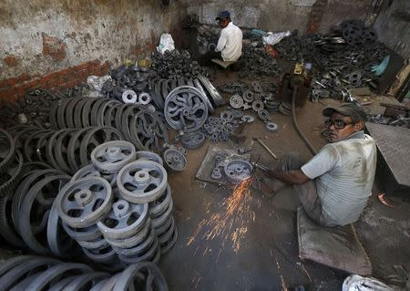 Workers grind iron bearings used in textile machinery inside a factory on the outskirts of Ahmedabad