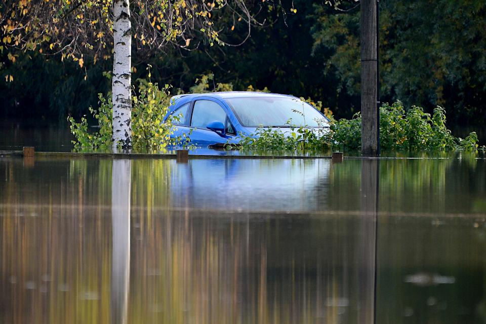 A car is almost completely submerged in Tewkesbury, Gloucestershire (SWNS)