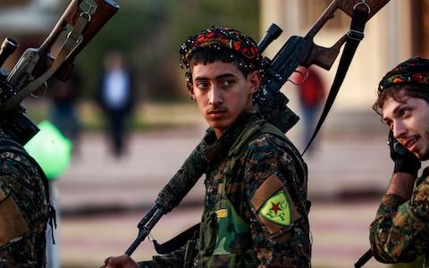 YPG fighter holds a sniper rifle on his shoulder as he attends the funeral of a slain commander in the northeastern city of Qamishli - Credit: AFP