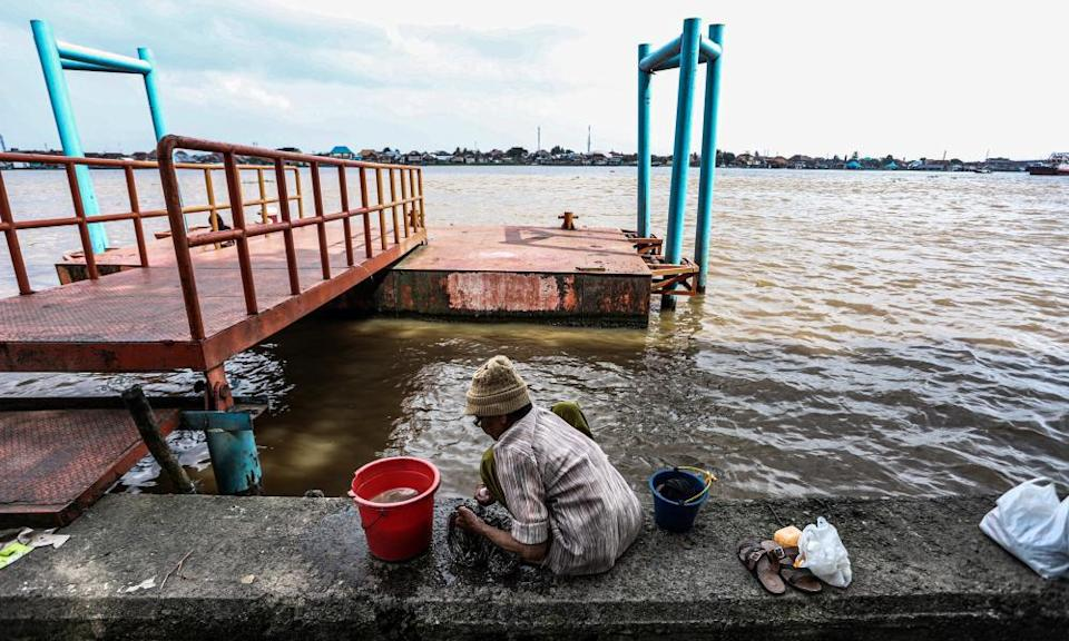A woman washes clothes near the river at a slum area in Palembang