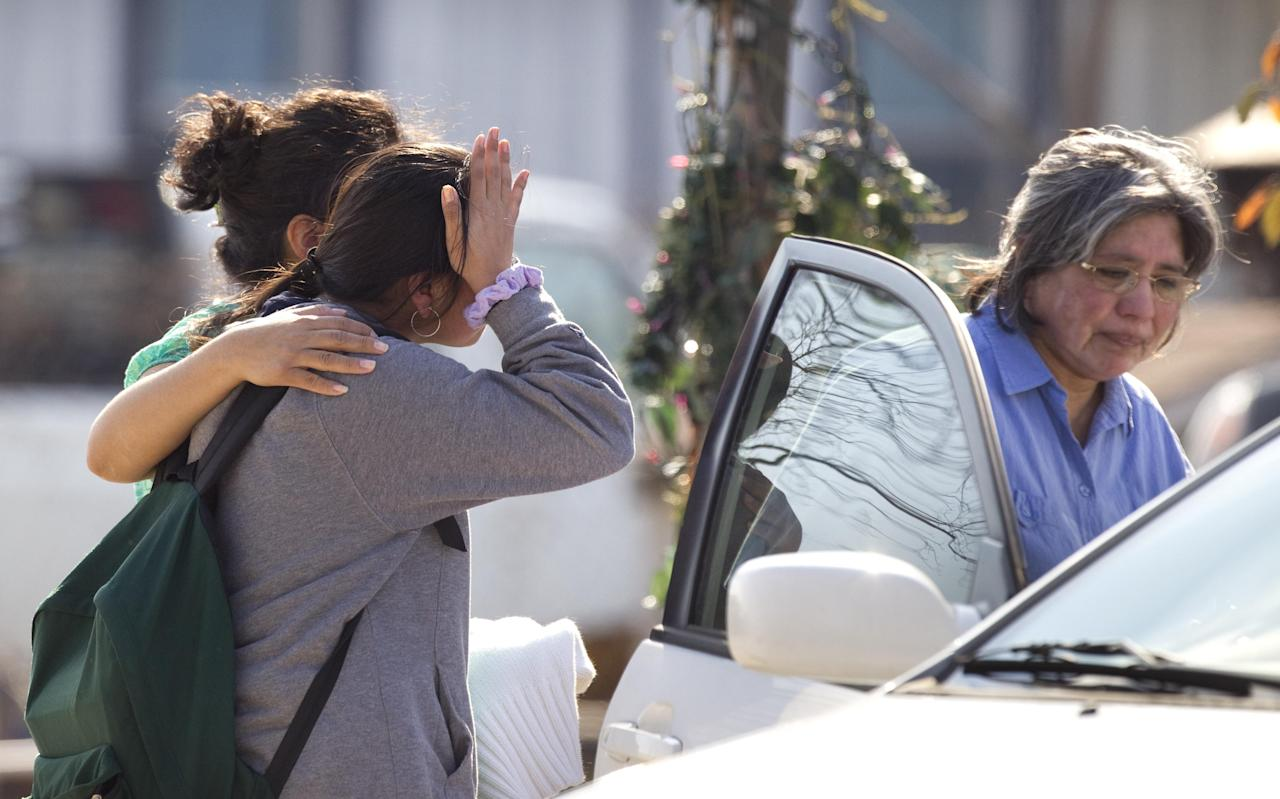 Ana Leal, left, embraces Lone Star College student Sabrina Cuellar after she was evacuated and picked up by her mother, Maria Cuellar, right, from the campus following a shooting at the north Harris County school Tuesday, Jan. 22, 2013, in Houston. Authorities say the shooting was the result of an altercation between two people, and at least one was a student. (AP Photo/Houston Chronicle, Brett Coomer) MANDATORY CREDIT