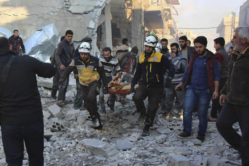 This photo released by the opposition Syrian Civil Defense rescue group, also known as White Helmets, which has been authenticated based on its contents and other AP reporting, shows Civil Defense workers evacuate a victim from site of airstrikes in the village of Balyoun, in Idlib province, Syria, Saturday, Dec. 7, 2019. Airstrikes on areas in the last major rebel stronghold in northwest Syria on Saturday killed at least 18 people, including women and children, and wounded others as a three-month truce crumbles, opposition activists said. (Syrian Civil Defense White Helmets via AP)