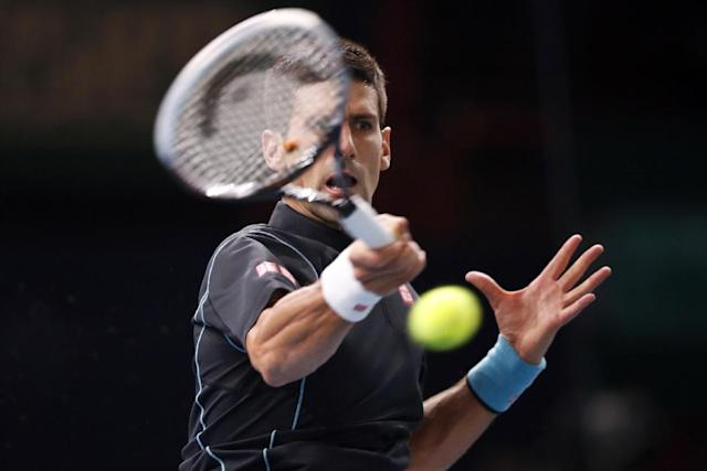 Novak Djokovic of Serbia returns the ball to France's Pierre-Hugues Herbert, during their second round match, at the Paris Masters tennis at Bercy Arena in Paris, France, Tuesday, Oct. 29, 2013. (AP Photo/Francois Mori)