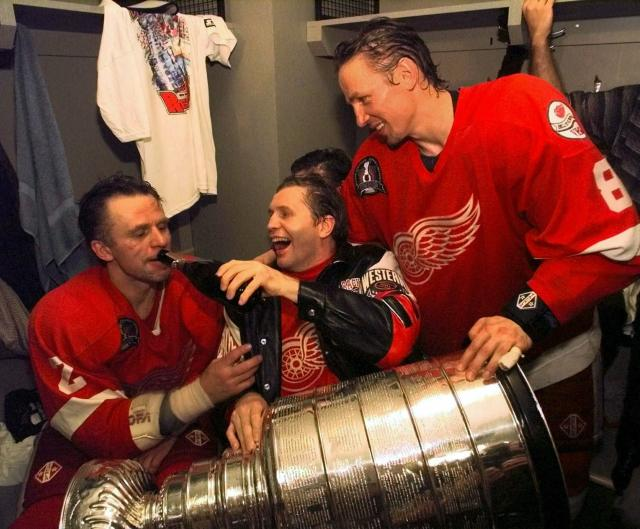 FILE - In this June 16, 1998 file photo, Vladimir Konstantinov, center, holds the Stanley Cup in his lap and pours champagne for defenseman Viacheslav Fetisov, left, as center Igor Larionov looks on in a post game locker room celebration after beating the Washington Capitals 4-1 in Game 4 to take the Stanley Cup at the MCI Center in Washington. More than two decades since Fetisov and the Russian Five shattered the myth that NHL teams couldnt win with players from a nation unpopular in North America, the St. Louis Blues Russian Two of Vladimir Tarasenko and Ivan Barbashev are one victory away from lifting the same Cup after being inspired by the generation of countrymen who endured so much to get there. (AP Photo/Wilfredo Lee, File)