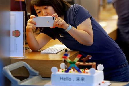 FILE PHOTO: A member of Apple staff takes pictures as new iPhone X begins to sell at an Apple Store in Beijing